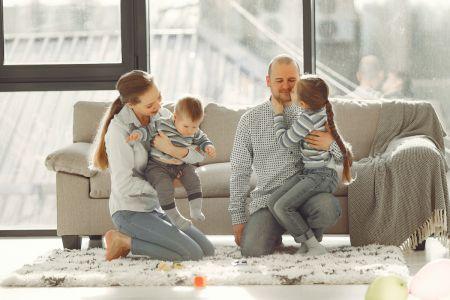 Eine Frau kniet auf dem Boden und hält ein Baby im Arm, daneben sitz ein Mann, der von einem Mädchen mit einem geflochtenen Zopf umarmt wird.